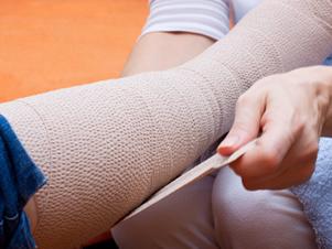 Pflegerin bandagiert den Fuss einer Patientin